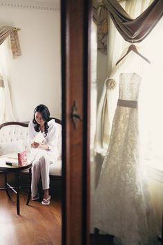 The bride is reading the love letter from the groom before getting into the wedding gown.