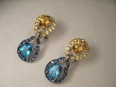 14K white gold earrings with gemstones. Each unique earring features one oval citrine, one oval blue topaz, numerous round yellow and blue sapphires