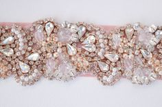 This Rose gold bridal belt is the perfect finishing touch to your bridal gown, pageant gown or other formal event gown. This intricate bridal belt features clear crystal rhinestones in a rose gold metal setting, beads (clear and champagne) and pearl detailing. This wedding belt features a ribbon sash that is 1.5 wide, and 72 long. Ties in back with a beautiful bow. Bling portion of the Bridal Belt applique is approx. 19.5 by 1.5. We can customize this belt to be at an additional length/w...
