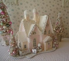 This pretty Putz style Christmas house is painted in yummy marshmallow colors of pale pink and cream. Faux smoke billows from the dual chimneys, and
