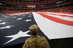 A member of the military holds a giant American flat during the national anthem before the first half of an NFL football game between the Atlanta Falcons and the Tampa Bay Buccaneers, Sunday, Sept. 11, 2016, in Atlanta.