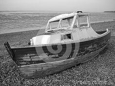 Decaying weather-beaten boat wreck left on the beach