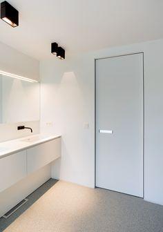 White interior door with invisible door frame and a built-in plexiglass door handle. This modern door is custom-made by Belgian brand Anyway Doors.