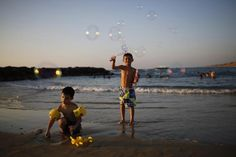 An Israeli child blow soap bubbles on the shore of the Mediterranean sea at the southern Israeli city of Ashkelon