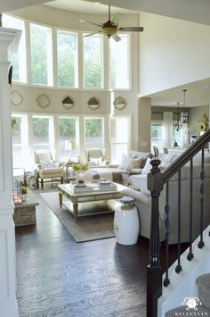 Kelley Nan: Form vs. Function in the Family Room: Balancing the Pretty with the Practical - Two Story Great Room with High Ceilings and Neutral Decor- Living Room Ideas with Mirrors Between two rows of windows
