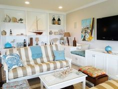 Lovely living room with sand colored striped fabric, beach mementos on the shelves and contrasting blue/aqua pillows for accent.