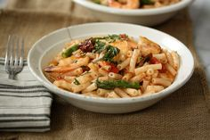 This spicy shrimp pasta salad recipe is an easy, healthy lunch with asparagus, cherry and sundried tomatoes, and gluten-free noodles.