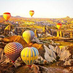 Aquele momento emocionante em que o balão começa a subir ao mesmo tempo em que o sol começa a nascer! Tudo vai ficando mais dourado e a sensação é de estar sobrevoando a superfície da Lua! Experiência que enche os olhos e fica para sempre guardada no coração! #cappadocia #honeymoon #luademel  #turquia #turkey #capadocia #travel #trip #balloons #viagem #casamento #wedding #noiva #noivado #noivos #amazing #beautiful #lunademiel #luxurytravel #luxury #luxwt #instagram #happy #sky