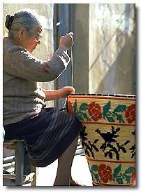 Alcuni oggetti di artigianato sardo - donna che lavora un cesto