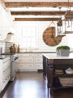 Farmhouse style kitchen with wooden beamed ceilings and white subway tile | Bradley E Heppner