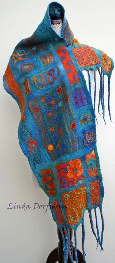 I nuno felted this multi colored scarf in shades of turquoise blue, orange, rust and amber hues with images of the southwest dancing around in my head. Dozens of mini collages are incorporated into this scarf. I accented each small panel with contrasting silk, wool roving, yarns and