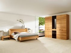 Large natural-wood bedroom with large light-wood wardrobe, white walls and ceiling