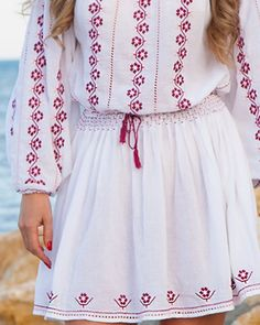 Let yourself be enthralled by the beauty of the Cherry Blossom, sewn by hand with masterly skill on this ethnic dress. This exquisite dress is made of white cotton and is decorated with floral patterns, embroidered with dusty purple and pink cotton. This alluring handmade dress is decorated with stylish embroidery and lace, made by hand. Feminine and fabulous, this long-sleeved dress is decorated on the chest, sleeves and on the bottom of the skirt with handmade embroidery and is creased…