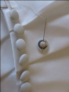 This article shows how to add the buttons to the dress, without any loops just over the flap of the zipper. If you combined this with the loops over the zipper then no need to find a pattern that just has buttons.