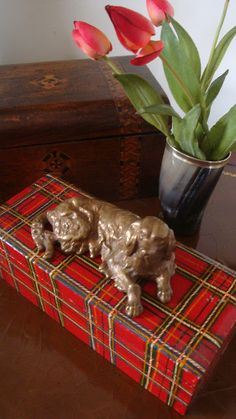 Little old brass dog resting  on plaid wooden box.  :)