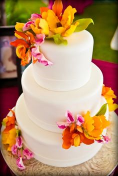 Floral white wedding cake. Kinda what I want for my anniversary, but with tiger lillies, dark purple gerbera daisies and red roses