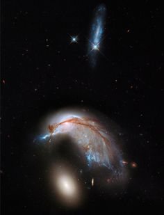 A fuller-frame image of Arp 142; notice the smaller blue galaxy in the process of being destroyed atop the frame. Image credit: NASA, ESA and the Hubble Heritage Team (STScI/AURA).