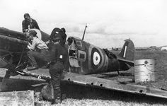 """Ground crew attend to Spitfire Mk I GR-A after a landing accident at RAF Pembrey on 22 July 1940. The pilot was Sgt Ronald H """"Ronnie"""" Fokes who returned from a night sortie when the port undercarriage leg collapsed. At the time, No 92 Squadron RAF used the code GR when based at the airfield and QJ when stationed at RAF Biggin Hill."""