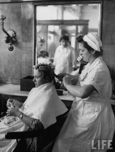 A woman getting her hair curled.