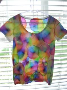 Tie-dye with less money and less mess!  Put a piece of cardboard between the 2 layers of the shirt. Rubber-band a portion of the tee onto the top of a cup to to hold it in place. Color a quarter-size circle in the middle of the portion. Drip drops of 90% isopropyl alcohol onto sharpie design and watch the colors spread!