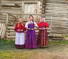 Restored and colored negatives by Sergei Mikhailovich Prokudin-Gorskii , photographer to the Tsar. Russian Peasant Girls, 1909. Young Russian peasant women offer berries to visitors to their izba, a traditional wooden house, in a rural area along the Sheksna River near the small town of Kirillov.