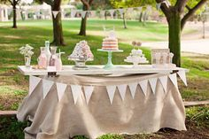 burlap covered food table for vintage style party with jadeite cake stands