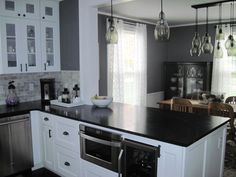 Like: dark countertops with gray walls and light fixtures a mix of gray glass and black fixtures. Light fixtures are at varying heights. The countertops work well with white cabinets. glass fronted cabinets add light because dishes are all white (wouldn't work for us!)   GardenWeb