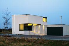 Das Haus steht als geschlossener weisser Kubus auf dem Grundstück, die an die Kanten geschobenen Fenster mit ihrem angedeuteten Passepartout wirken wie Bilder | Jöllenbeck + Wolf ©Thomas Ott Fotografie, Mühltal