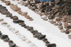two artists have realized a robotic apparatus that autonomously organizes river pebbles based on data collected about their geological age.