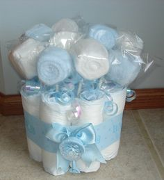 """It's a boy mini diaper cake with washcloth lollipops~This cute diaper cake is a great way to celebrate a new baby boy! Perfect centerpiece for baby shower. It is created with size one diapers, blue """"it's a boy"""" ribbon, a cute decorative rattle and bow. Inside are 10 white and blue washcloth lollipops and white and blue irridescent ribbon."""