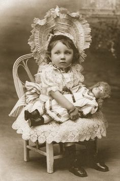 Darling antique photo of a toddler girl with her doll, circa 1900.
