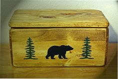 "A Bear In The Woods Handmade Storage Box. This handmade rustic storage box is the perfect addition to your cabin or lodge to store those little things that just seem to never be put away. Each box comes with a the hand painted picture of a bear and two trees in the front with a picture of a bear on each side. The dimensions are: 12 1/2"" wide x 7"" deep x 6"" high. Each piece is finished with a honey pine oil and a semi-gloss lacquer."