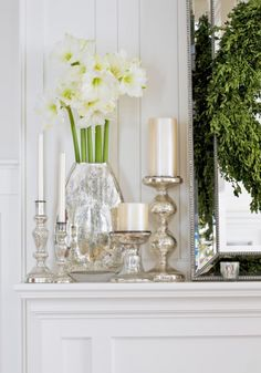 Glittering Accents  Surfaces that catch the light—like mercury glass, silver, and mirrors—are a gorgeous way to add some sparkle to a room and make the most of natural light. On this mantel, pearlescent candles mingle with silver details and fresh paperwhites for a clean look.