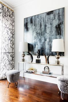 Living room vignette with large moody modern art, a glass table, matching silver lamps and lamb stools