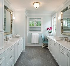 Exquisite blue and gray master bathroom features facing pale blue washstands separated by slate herringbone floor tiles and accented with polished nickel pulls and white quartz countertops holding antique polished nickel faucets positioned under beaded beveled vanity mirrors mounted to pale blue walls lit by nickel sconces and a beaded flush mount.