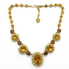 Description A beautiful 1950s Regency style necklace featuring rhinestone panels in shades of amber and yellow. The necklace is finished with an ad...