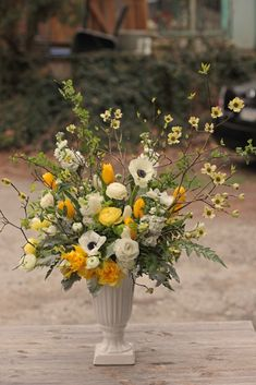 April arrangement featuring dogwood, tulips, anemones, ranunculus, and daffodils