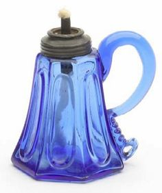 Small early handled whale oil lamp, probably Boston and Sandwich Glass Works. Seven-sided elongated loop pattern in briliant sapphire blue, sheared rim with applied pewter collar and burner, smooth base. Massachusetts, circa 1840-1860