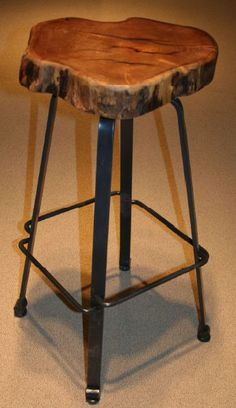 Hand forged metal is shaped and hammered into a solid bar stool base. An organic shaped natural mesquite slab is used for the seat. The combination of natural wood and solid steel is a stool that will fit comfortably into an industrial decor or rustic cabin.  They will also work well in ranch, lodge,