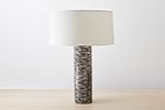 The mottled look of this textural table lamp is achieved by applying a charcoal wash over the base ivory glaze. Sold with an unlined ivory drum shade.