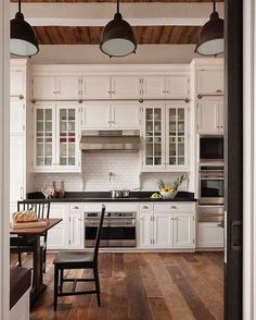 Country white kitchen with glass fronted cabinets black counters, antique hardwood floors with a high ceiling