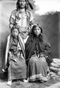 Ute group portrait Studio portrait of Native Americans (Ute); shows a man and a woman (the mother of Ellen Watt), and her daughter (possibly), Daisy House Eagle. The man wears braids, a choker, breastplate, and a shirt; the women wear dresses and shawls.
