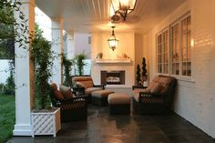 Dreamy outdoor covered patio with painted brick walls and white brick outdoor fireplace. The outdoor living space features a beadboard ceiling lit by a pair of traditional style iron and glass lanterns. The seating arrangement features outdoor rattan armchairs, sofa and ottomans. Spiraling topiaries flank the fireplace while climbing plants in white planters flank the patio columns.