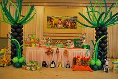 Jungle / Madagascar theme tree balloon columns for a boy's first birthday party.