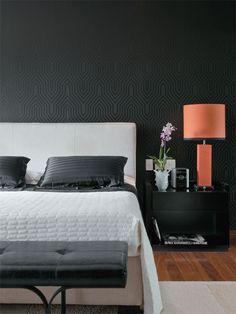Com grafismo formado por preto fosco e brilhante, o papel (Miranda Green) reveste a parede do quarto. A cama tem cabeceira revestida de linho (Empório Beraldin). O abajur é Butik.
