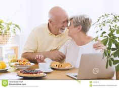 Lovely elderly couple hugging and looking into each other`s eyes sitting at a table with laptop, cake, buns, lemons and plant
