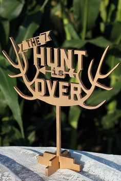 """The Hunt is Over!! This topper measures 8 1/2"""" x 9"""". It is shown in a rusty copper and soft gold in photos.  All our cake toppers are made out of 1/4″ hardwood for a smooth finish. They can be bought painted in a color of your choice or in a natural wood. We finish them with a food safe coating. Even though we call them cake toppers they can be used in floral arrangements, centerpieces, wreaths, or as a table top decoration. Wedding, hunting, camo, bridal shower, rustic, antlers, deer…"""