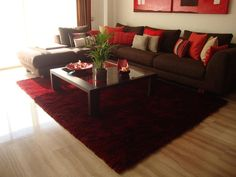 interesting red carpet living room with glass table also brown sofa with red pillows also wooden floor for modern house.