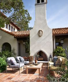 The courtyard in this Hollywood home features a fireplace with a 17th-century armorial cartouche found at Bonhams. The teak cocktail table is by Holly Hunt and the flooring is of reclaimed terra-cotta tiles.