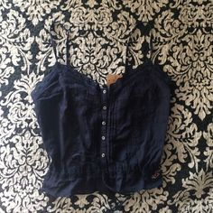 Navy Hollister Tank Never worn and it perfect condition. Perfect for summer and showing a little mid-drift! (Not a crop top). Adjustable ties in the front. Cleaning out my closet everything must go!! No trades but price is negotiable!! Hollister Tops